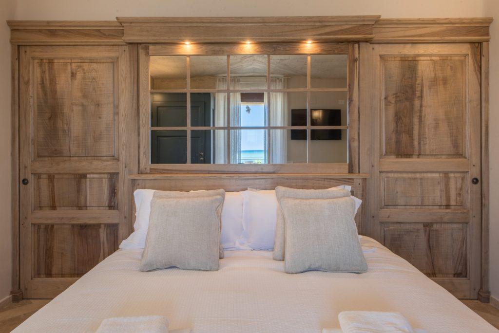 Camera da letto, in legno e pietra naturale. Testiera letto a specchio. Villa Galatea, San Vincenzo - GH Lazzerini, Toscana